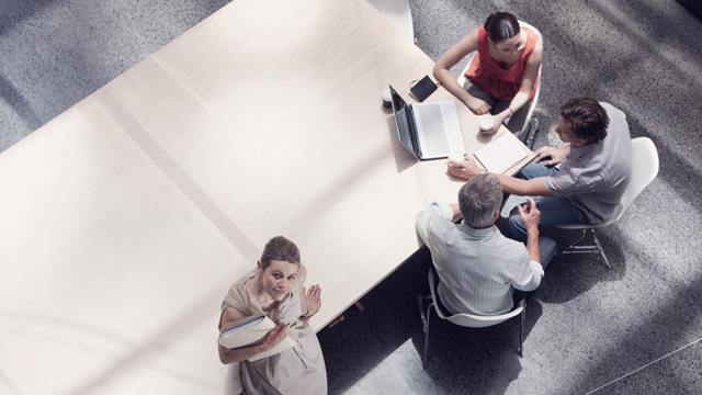 Business meeting with four people talking in an office