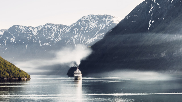 Cruise ship in Nordic Fjord with snow on the mountains