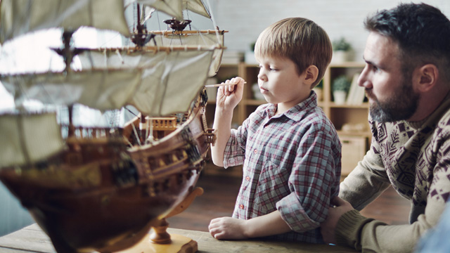 Father and son at home looking at old miniature boat