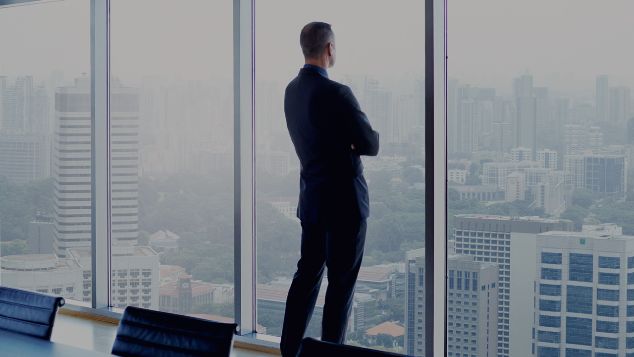 Businessman in meeting room looking out through the window