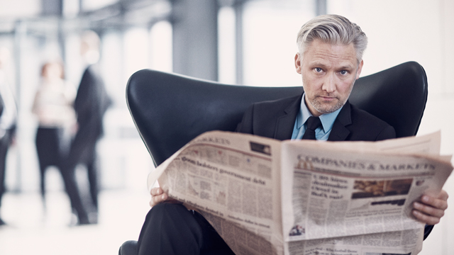 Man reading newspaper in chair