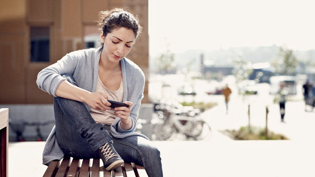 Young woman with mobile outdoor - Small